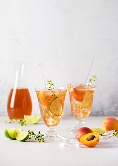 Коктейль из свежих абрикосов с ледяным лаймом и лимонным тимьяном в освежающем стакане