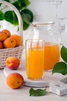 Свежий абрикосовый сок в стекле и графине со спелыми абрикосами на деревянном столе против белой кирпичной стены с зелеными листьями. выборочный фокус. крупный план.