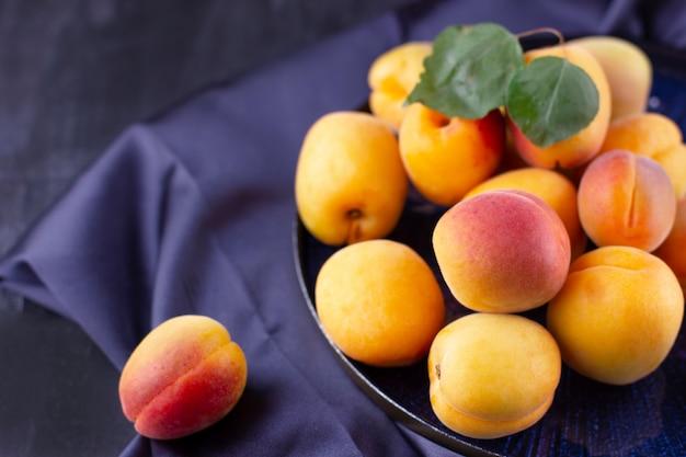 Свежий абрикос на темной шелковой ткани