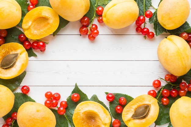 Fresh apricot and red currant berries with leaves on a light tab. background copyspace