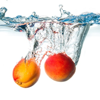 Fresh apricots falling in water