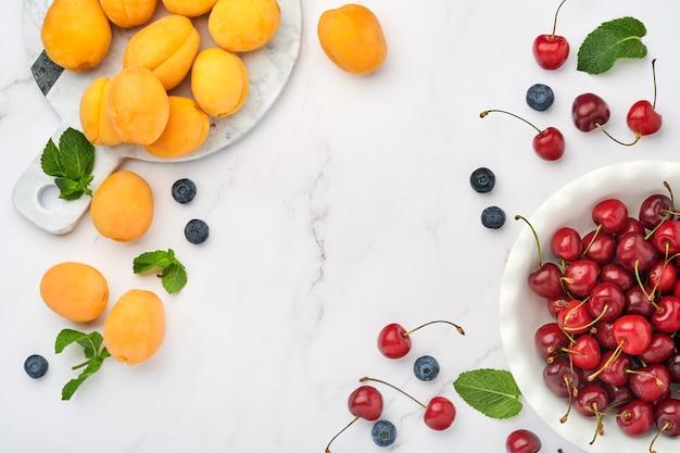 Свежие абрикосы, красная вишня и ежевика на белом мраморном фоне. вегетарианский, потеря веса, концепция чистого и здорового питания. вид сверху. скопируйте пространство.