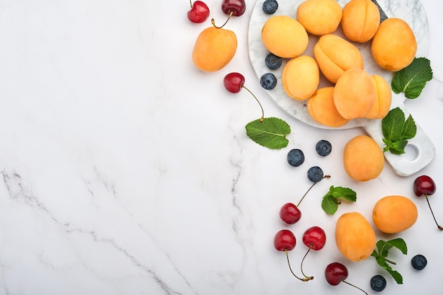 Fresh apricots, red cherry and blackberry on white marble background. vegetarian, weight loss, clean and healthy eating concept. top view. copy space.