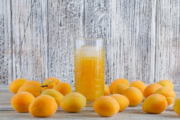 Свежие абрикосы с ледяной сок вид сбоку на деревянный стол