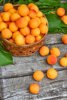 Fresh apricots with leaves closeup isolated on wooden background.