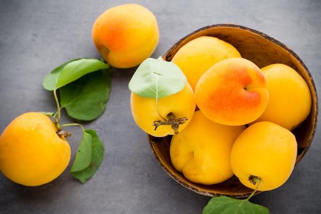 Свежие абрикосы с листьями на старом деревянном столе.