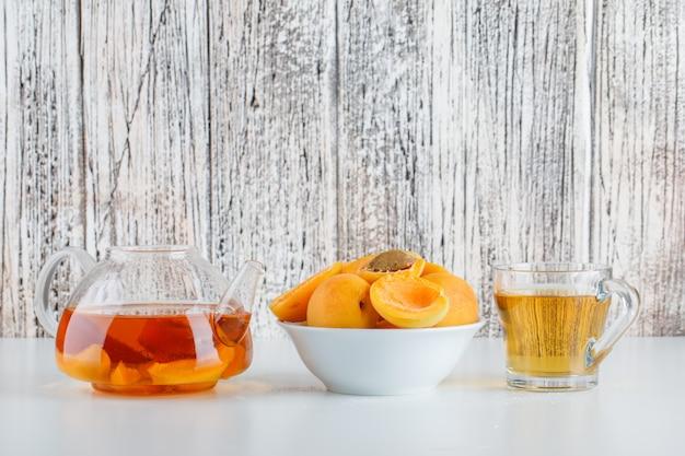 Свежие абрикосы с чаем в миску на белый и деревянный стол, вид сбоку.