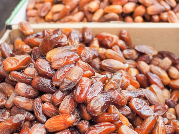Fresh arabic dates or date palm fruit for sale in farm market.