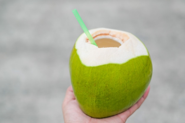 Fresh aromatic coconut juice, coconut fruit in hand with blur background.
