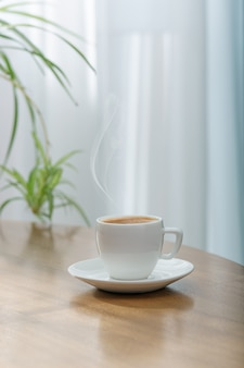 Fresh aromatic coffee in a white ceramic cup on a wooden table.