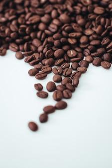白い背景で分離された新鮮な芳香の焙煎コーヒー豆