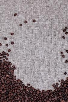 ベージュの黄麻布の背景に散らばっている新鮮な芳香の焙煎コーヒー豆上面図