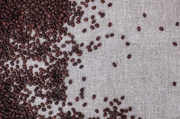 ベージュの黄麻布の背景に散らばっている新鮮な芳香の焙煎コーヒー豆上面図 Premium写真