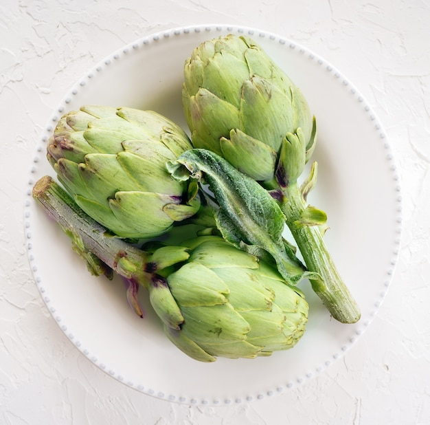 Fresh artichokes on the white plate,  top view