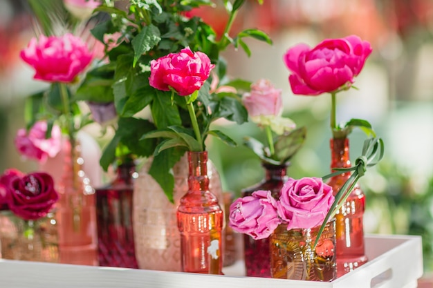 Fresh and artificial roses in different vases