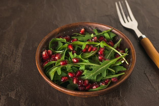 신선한 arugula 돌 표면에 그릇에 석류 씨앗과 나뭇잎. 다이어트 채식 샐러드.