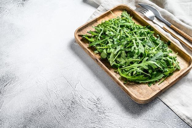木製のボウルに新鮮なルッコラサラダ。灰色の背景