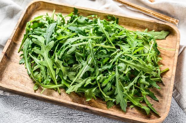 木製ボウルで新鮮なルッコラサラダ。灰色の表面。上面図