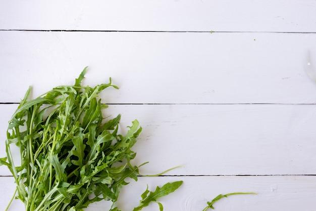 Свежие листья салата рукколы лежат на деревянном столе. под текстом