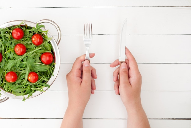 Салат из свежей рукколы с помидорами черри в миску на белом фоне деревянные. руки с ножом и вилкой.