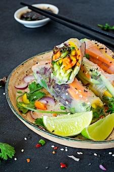 Свежая азиатская закуска спринг-роллы (нем) из рисовой бумаги и сырых овощей. вьетнамская кухня