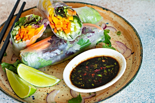 Fresh asian appetizer spring rolls (nem) made from rice paper and raw vegetables
