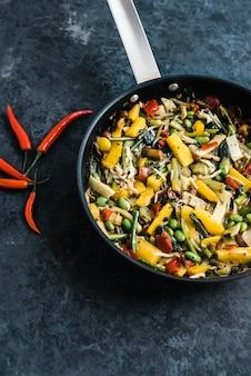 Fresh asian vegetables mix, thai wok in a black pan on the black