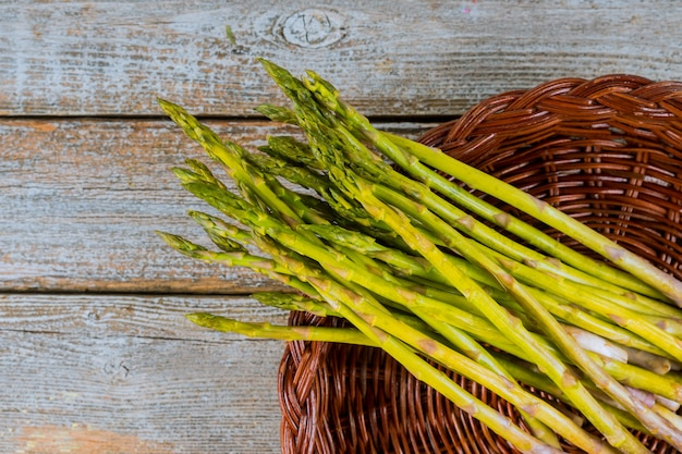 Fresh asparagus in brown basket on wood table.