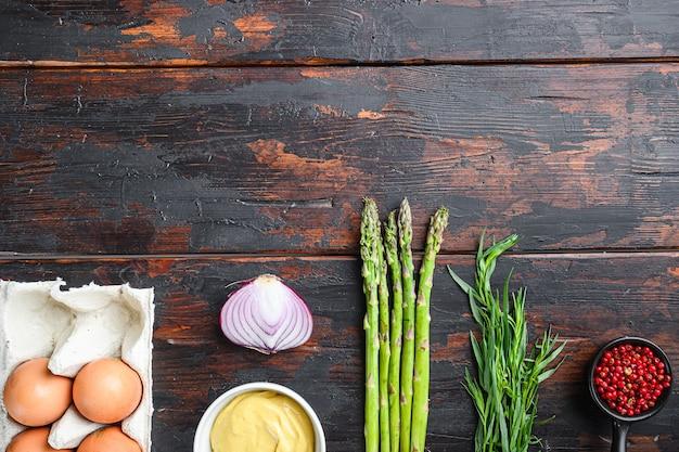 Свежие яйца спаржи и французские ингредиенты заправки с дижонской горчицей, луковый тарагон на темном деревянном старом фоне, вид сверху с пространством для текста.