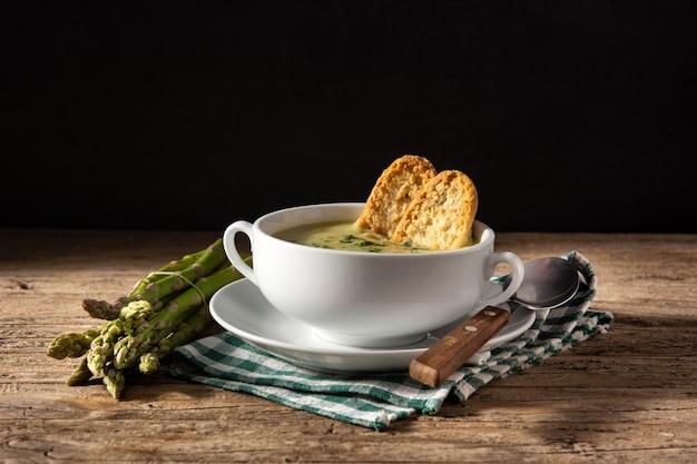 木製のテーブルに新鮮なアスパラガスのスープ