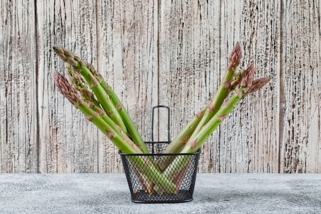 Fresh asparagus stems in a black colander on grungy grey and wooden wall