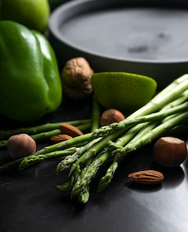 Fresh asparagus with green vegetables on an elegant dark background