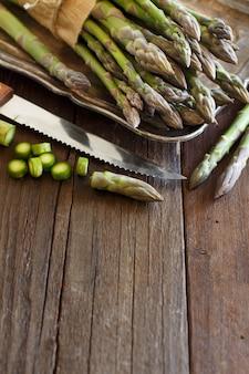 木製のテーブルにナイフで新鮮なアスパラガスをコピースペースでクローズアップ