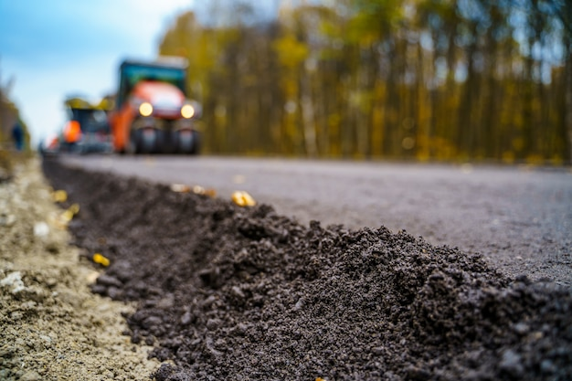 Fresh asphalt on highway construction site. industrial pavement machine laying.
