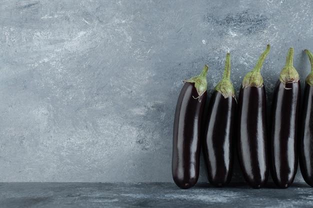 Fresh aubergine row on grey background.