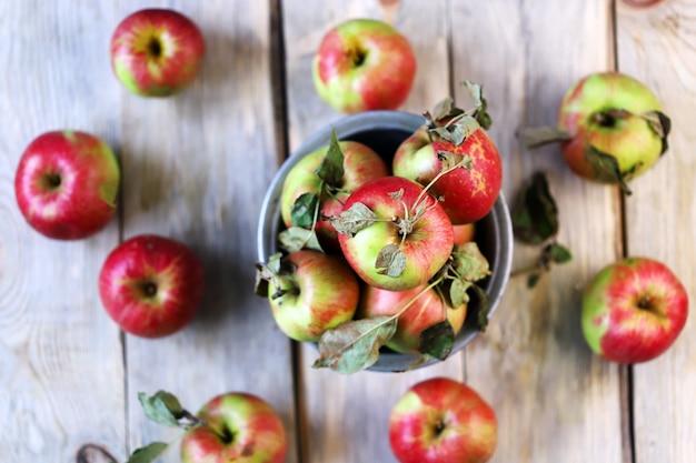 木の表面のボウルに新鮮な秋のリンゴ。