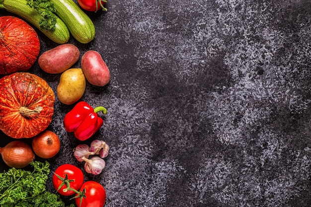 Fresh autumn vegetables for cooking on a dark background, top view.