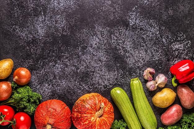 暗い背景、上面図で調理するための新鮮な秋の野菜。