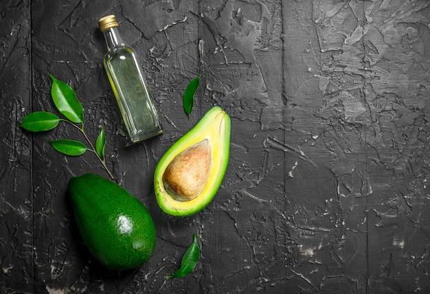 Fresh avocado and a bottle. on black rustic.
