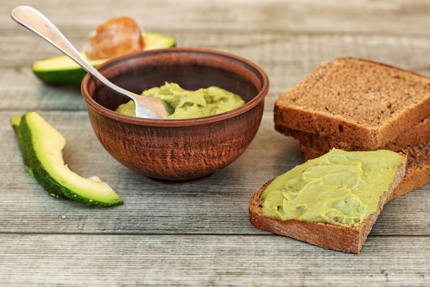 Fresh avocado cream in bowl, bread slices on grey wooden background