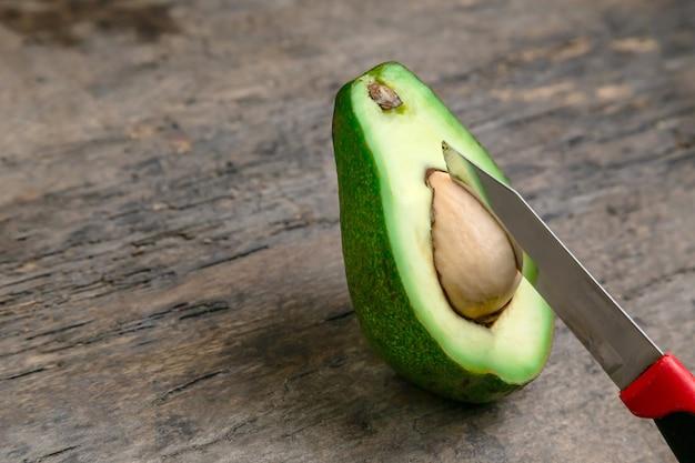 新鮮なアボカドはナイフの背景を持つ木の板の上半分にカット