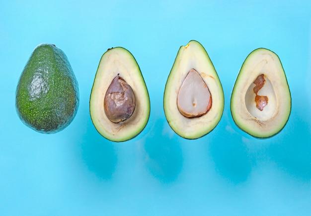 Свежие половинки авокадо с семенами летать на синем фоне