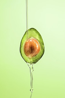 Fresh avocado and oil on green background