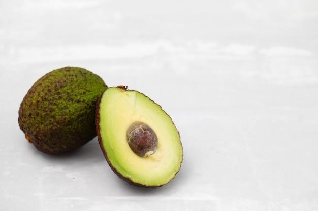 Свежий авокадо на керамическом фоне