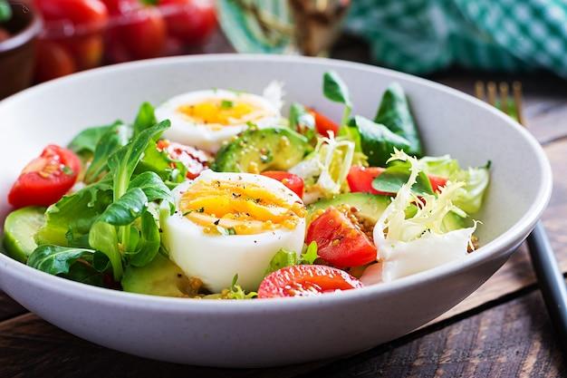 Fresh avocado salad with tomato, avocado, boiled eggs and fresh lettuce