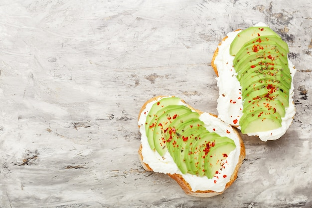 Свежий авокадо, нарезанный тостами со сливочным сыром