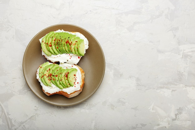 Fresh avocado sliced on two avocado toasts with cream cheese on sandwich