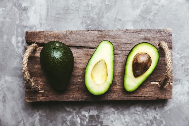 Fresh avocado sliced over vintage wooden background close up. ripe green avocado fruit on wood board.