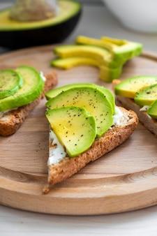 Гренки из свежего авокадо с кусочками мягкого сыра, авокадо, солью и перцем на ржаном хлебе на завтрак