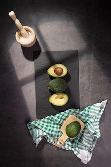 Свежие авокадо на темном фоне. вид сверху.